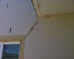 Large cracking over the doorway in wall.
